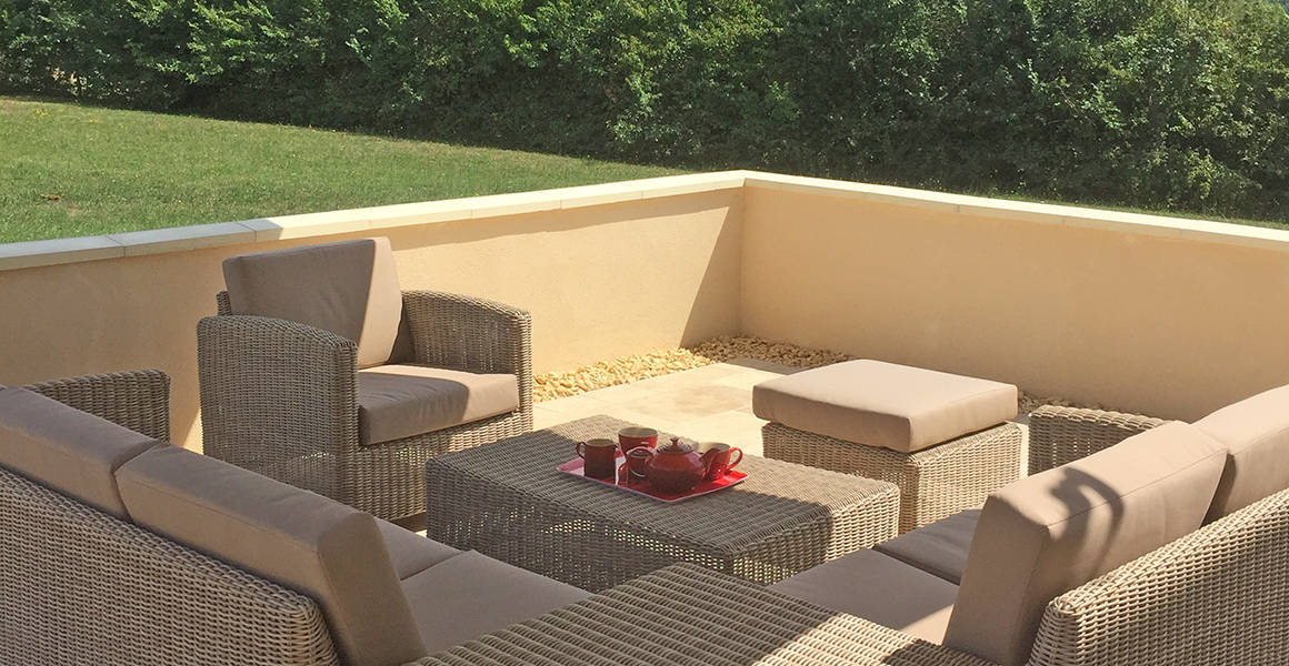 Comfortable outdoor furniture on the terrace to the side of the house